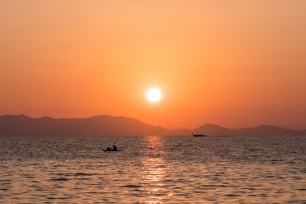 Beautiful sea sunset with silhouettes of fishing boats against the rocky coast Premium Photo