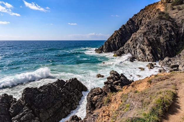 Скалистый пляж с видом на море и мыс байрон-бей Premium Фотографии