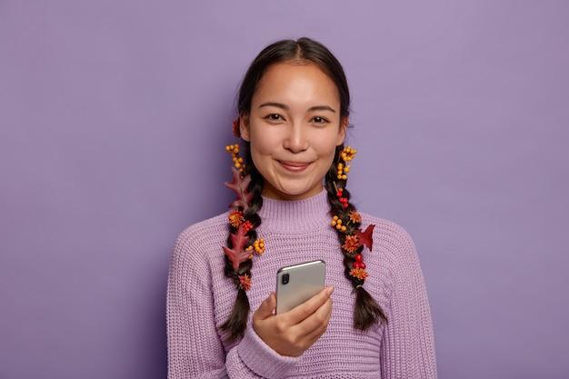 아름다운 시즌 개념. 매력적인 아시아 여성은 자연의 아름다움을 가지고 있으며, 가을 낙엽과 함께 두 개의 주름으로 빗질 한 검은 머리카락, 가을의 아늑함을 즐기고 여가 시간에 현대적인 스마트 폰을 사용합니다. 무료 사진