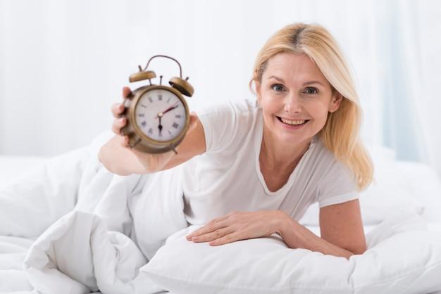 Красивая старшая женщина держа часы Бесплатные Фотографии