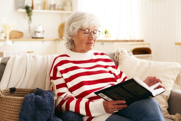 Bella donna senior con i capelli grigi godendo la pensione, seduto sul divano in soggiorno, leggendo un romanzo interessante. femmina caucasica anziana in occhiali rotondi che si rilassano a casa con il libro Foto Gratuite