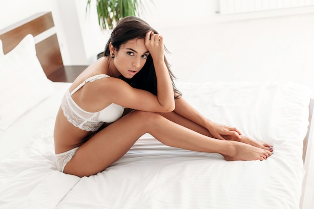 d658ba7945b Beautiful sensual portrait of young brunette woman sitting in her white bed  morning style sexy young