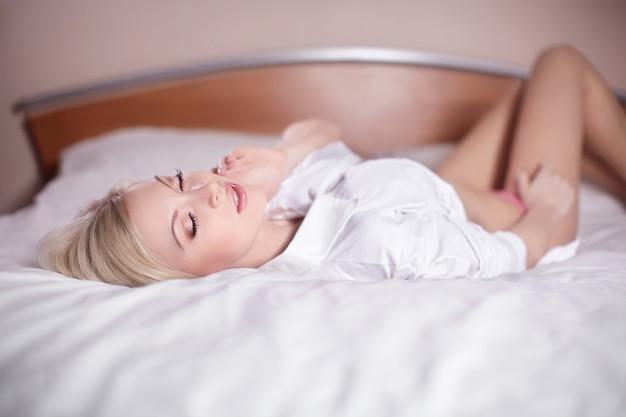 벌거 벗은 침대에 누워 아름다운 관능적 인 섹시한 젊은 금발의 여자 무료 사진