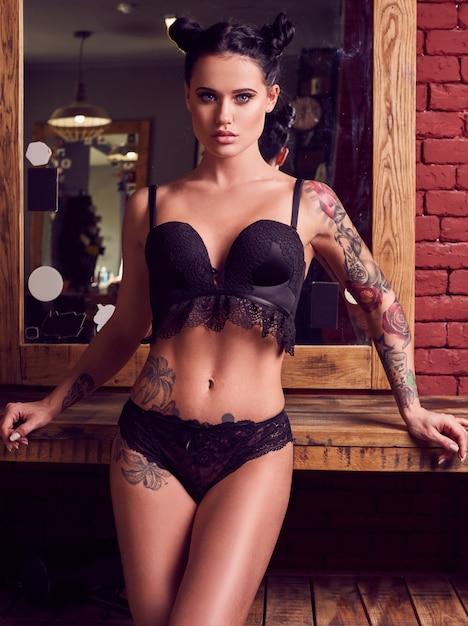 Красивая чувственная женщина с татуировками в нижнем белье в парикмахерской Premium Фотографии