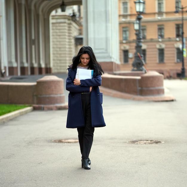 Beautiful serious smart girl brunette student holding notebooks and textbooks, goes walking at university Premium Photo