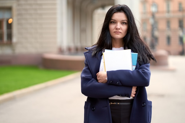 Beautiful serious smart girl brunette student holding notebooks and textbooks, stands at university Premium Photo