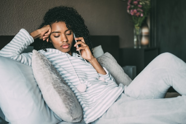 Beautiful serious thoughtful and sad black woman with curly hair using smartphone on bed Premium Photo