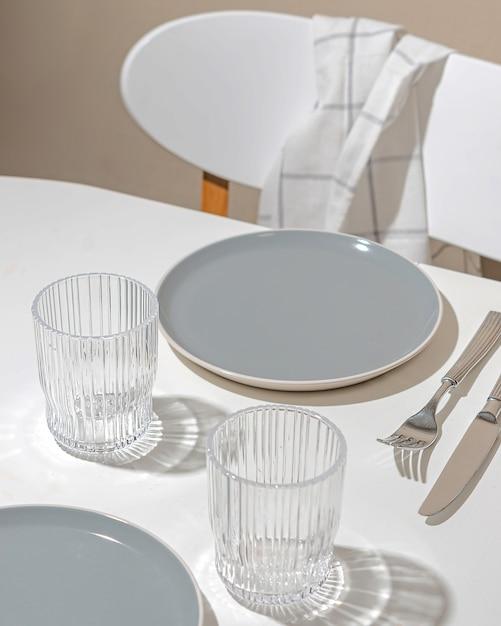 Beautiful setting - empty plates and glasses on the table. hard sunlight light Premium Photo