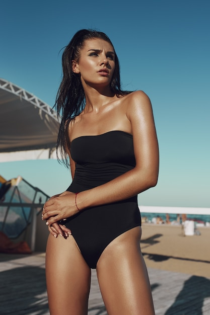 A beautiful sexy amazing young woman in a black swimsuit posing on the beach. long hair, black bikini, fashion, red thread Premium Photo
