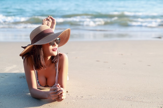 Beautiful and sexy asian girl with hat lying down on the beach Premium Photo