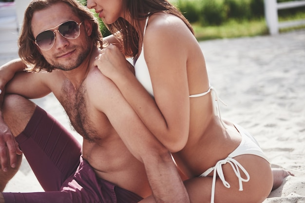 Bella coppia sexy ragazzo e ragazza che indossa il costume da bagno quando sulla spiaggia. romanticamente sdraiato sulla sabbia. Foto Gratuite