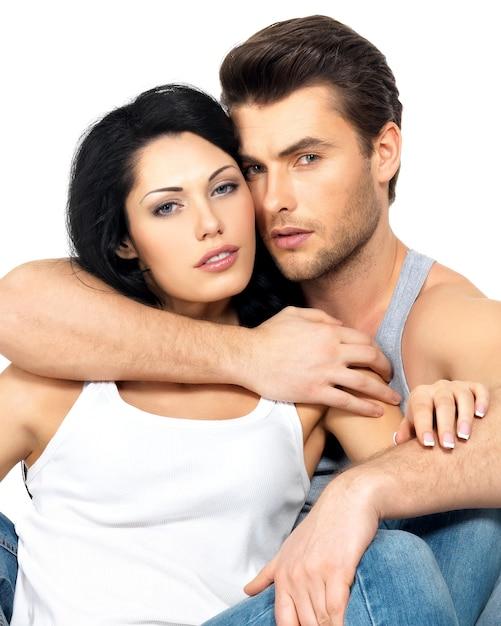 Красивая сексуальная влюбленная пара на белом, одетая в синие джинсы и белую майку Бесплатные Фотографии
