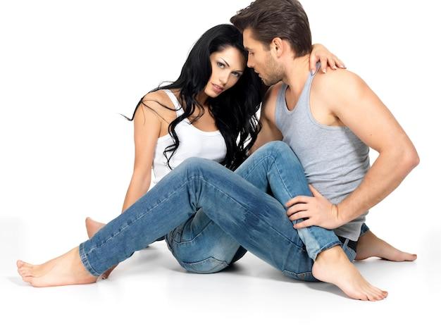 ブルージーンズと白いアンダーシャツに身を包んだ白いスペースで恋に美しいセクシーなカップル 無料写真