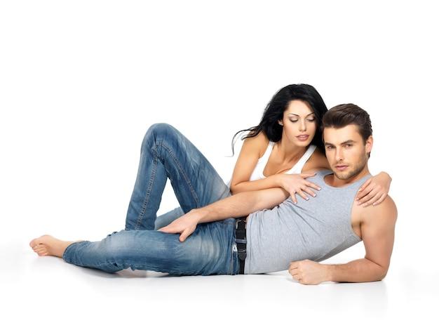 Красивая сексуальная влюбленная пара на белом пространстве, одетая в синие джинсы и белую майку Бесплатные Фотографии