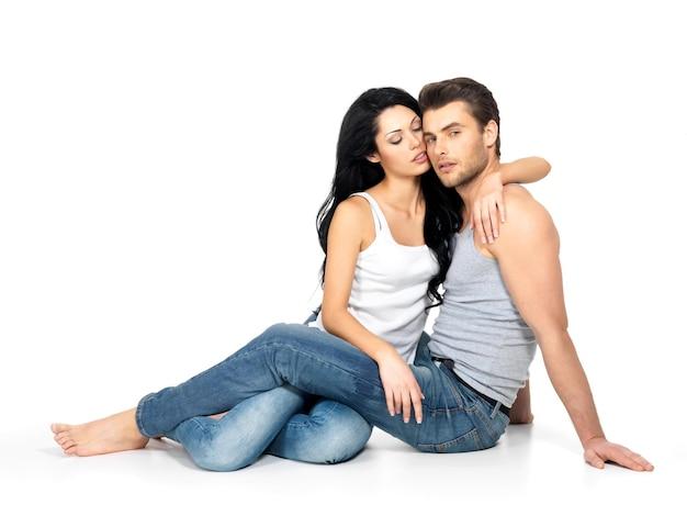 Красивая сексуальная влюбленная пара на белой стене, одетая в синие джинсы и белую майку Бесплатные Фотографии