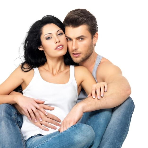 Bella coppia sexy innamorata sul muro bianco vestita di jeans blu e maglietta bianca Foto Gratuite