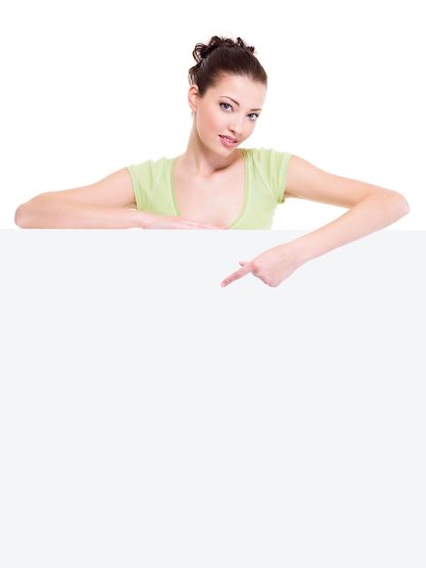 Красивая сексуальная женщина cuacasian под белым пустым знаменем указывает указательным пальцем на нем Бесплатные Фотографии