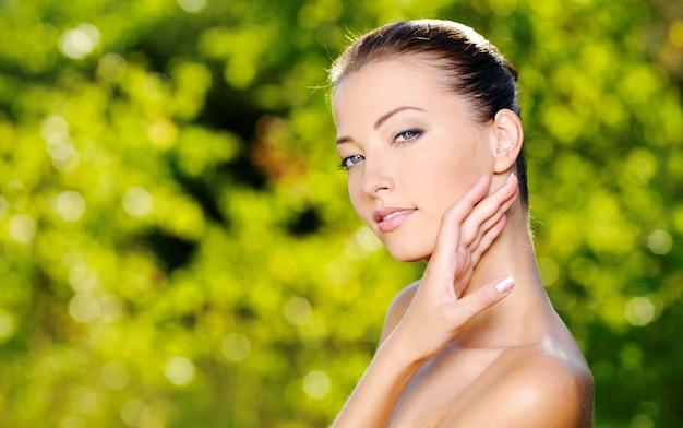 新鮮な健康肌を持つ若い女性の美しいセクシーな顔。自然にポーズをとる女性。彼女の体をなでるモデル。 無料写真