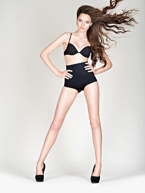 검은 란제리를 입고 긴 머리를 가진 아름 다운 섹시 한 여자. 완벽한 몸매를 가진 하이힐에 여자 긴 다리. 검은 팬티를 입은 스튜디오에서 Fahsion 모델 포즈 무료 사진