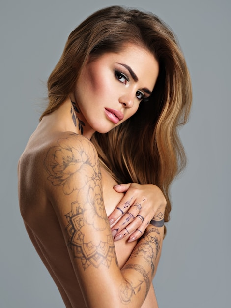 Beautiful sexy girl with a tattoo on the body. portrait of young adult woman girl with brown hair. sexy female with nude body and covers breast with arms Free Photo