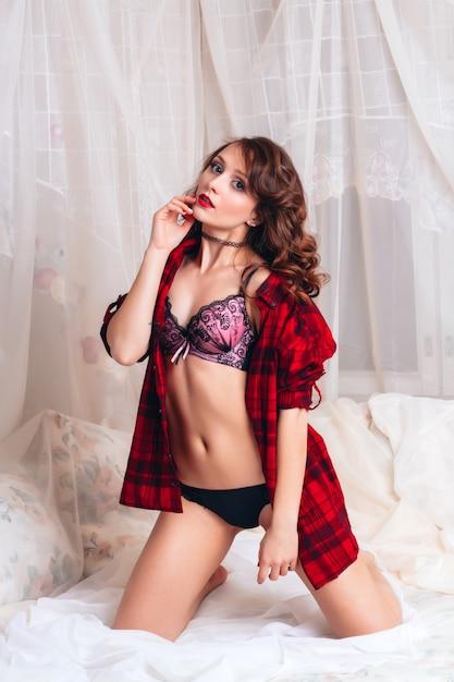 흰 침대에 벨트와 속옷에 아름 다운 섹시 벗은 여자. 매력적인 매력적인 여성의 에로틱 사진 촬영 프리미엄 사진