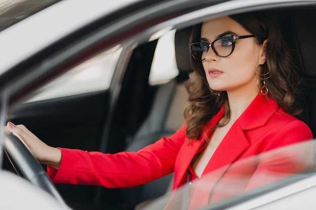 白い車で運転、眼鏡、ビジネスレディスタイルの赤いスーツの美しいセクシーな金持ちのビジネス女性 無料写真