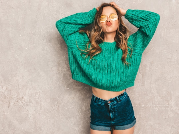 Beautiful sexy smiling gorgeous girl in green trendy sweater. woman posing in round sunglasses. model having fun and giving kiss Free Photo