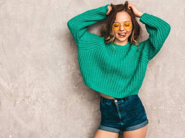 Beautiful sexy smiling gorgeous girl in green trendy sweater. woman posing in round sunglasses. model having fun and showing her tongue Free Photo