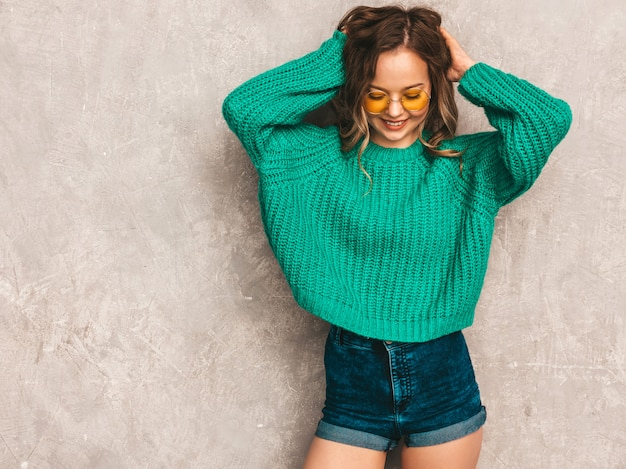 Beautiful sexy smiling gorgeous girl in green trendy sweater. woman posing in round sunglasses. model having fun Free Photo