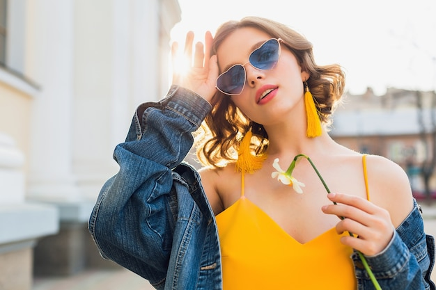 Beautiful sexy stylish woman in yellow stylish dress wearing denim jacket, trendy outfit, spring summer fashion trend, sunny, blue sunglasses, street fashion, hipster style, fashionable accessories Free Photo