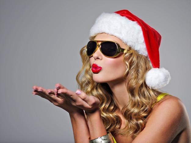 サンタの帽子で笑っている美しいセクシーな女性。かわいい女の子がキスを送ります。魅力的な若い女の子は小さなクリスマスツリーを保持しています-スタジオでポーズをとる 無料写真