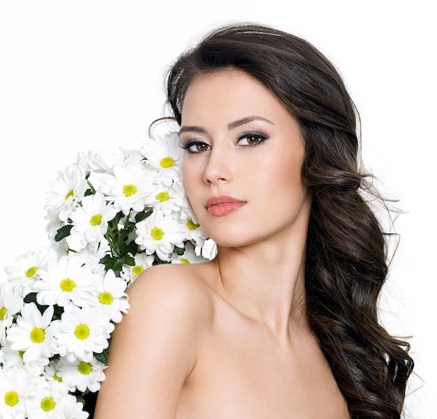 Bella donna sexy e fiori bianchi vicino al suo corpo - sfondo bianco Foto Gratuite