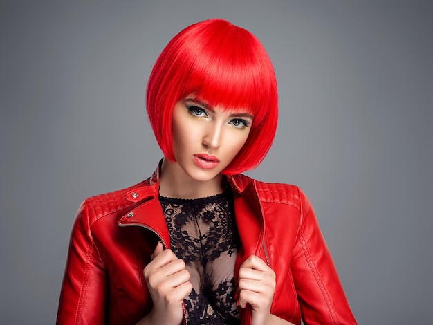 Beautiful sexy woman with bright red bob hairstyle. fashion  model. sensual  gorgeous girl in a leather jacket. stunning face of a pretty lady. Free Photo