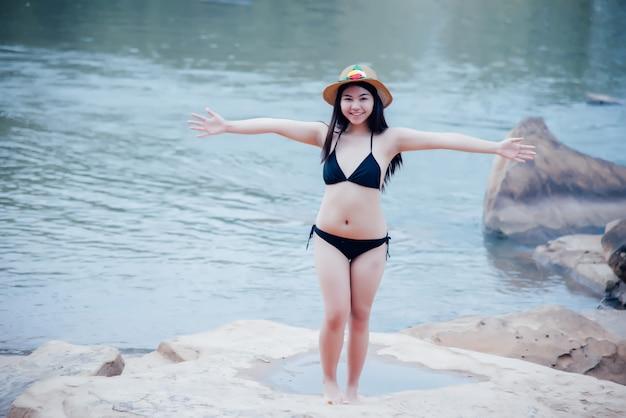 Beautiful sexy young woman in bikini at rock of waterfall Free Photo