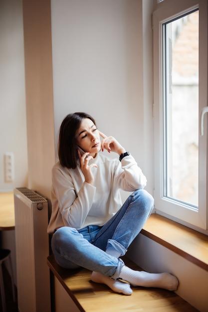 Красивая короткошерстная дама в синих джинсах сидит на подоконнике и пишет сообщение на смартфоне дома Бесплатные Фотографии