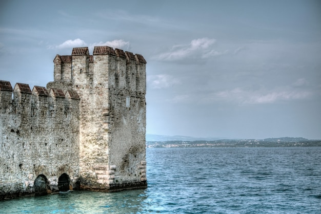 Beautiful shot of an ancient historic building in the ocean in sirmione, italy Free Photo