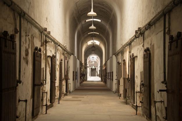 Bella ripresa di un corridoio ad arco in un vecchio edificio abbandonato con molte porte Foto Gratuite
