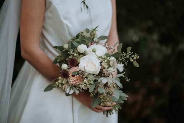Beautiful shot of a bride wearing wedding dress holding a flower bouquet Free Photo