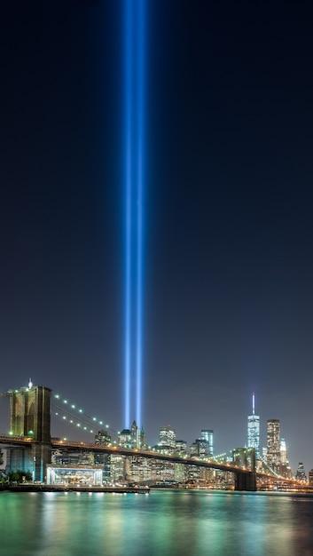 Bella ripresa del parco del ponte di brooklyn di new york city negli stati uniti con un raggio di luce blu nel cielo Foto Gratuite