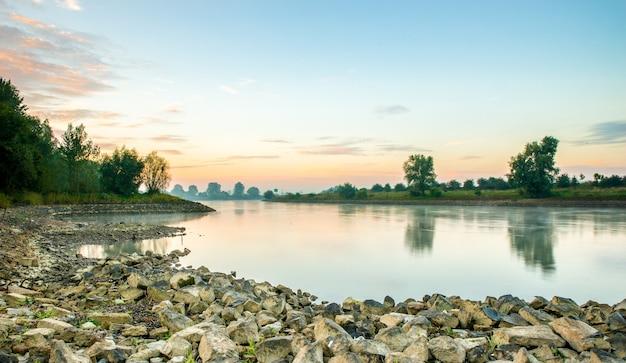 Bella ripresa di un lago calmo circondato da alberi durante un tramonto Foto Gratuite
