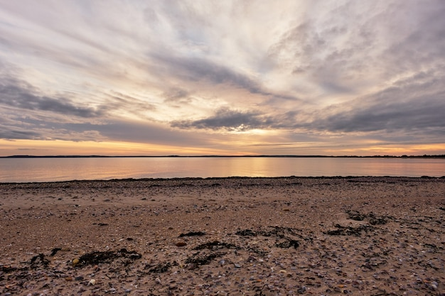 Bella ripresa di un oceano calmo con uno scenario del tramonto in un cielo blu nuvoloso Foto Gratuite