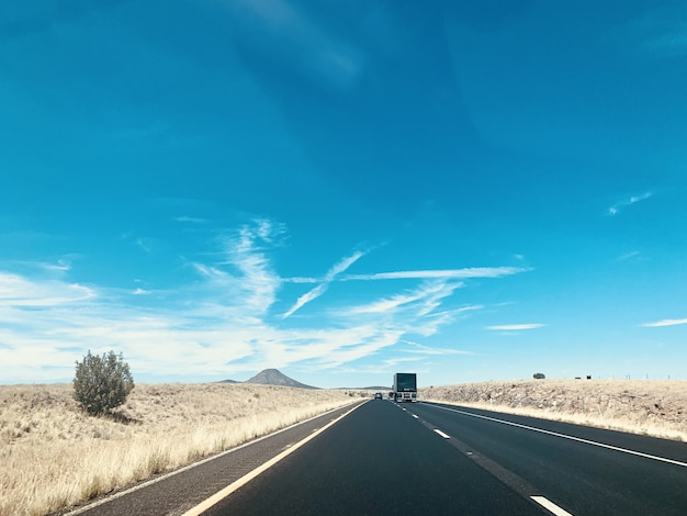 Beautiful shot of the cars on the road under the blue sky Free Photo