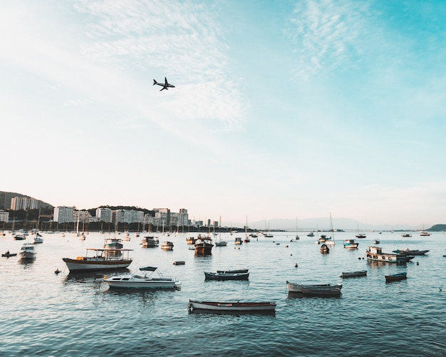 Beautiful shot of coast of an urban coastal city with many boats and an airplane flying in the sky Free Photo