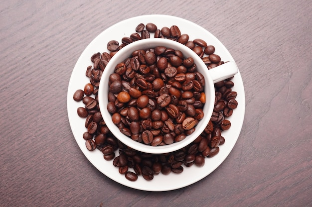 Beautiful shot of coffee beans in the white cup and plate on a wooden table Free Photo