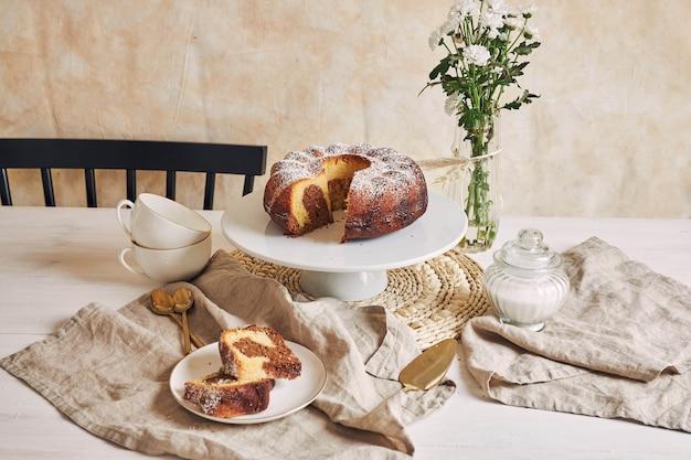 Bella ripresa di una deliziosa torta ad anelli posta su un piatto bianco e un fiore bianco vicino Foto Gratuite