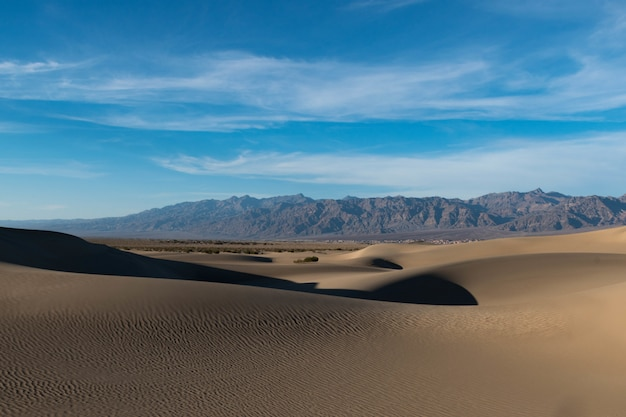 Bello colpo di un deserto con le tracce sulla sabbia e le colline rocciose sotto il cielo calmo Foto Gratuite