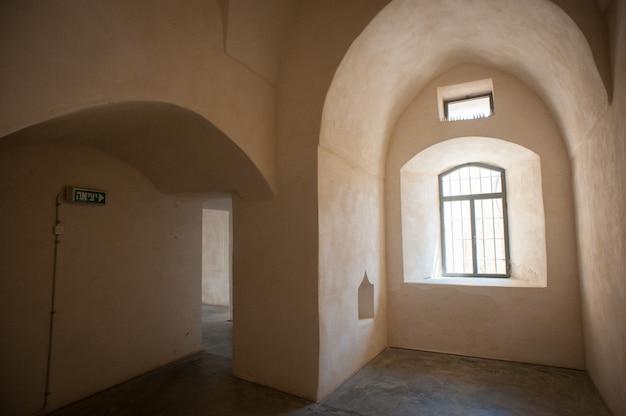 Bella ripresa di un interno di un edificio vuoto con pareti beige di finestre e un segnale di uscita Foto Gratuite