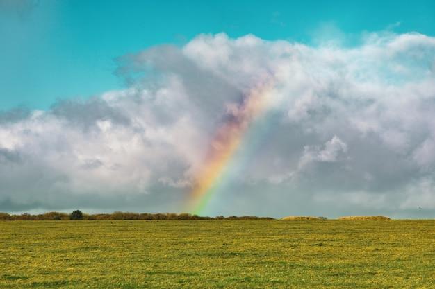 Bella ripresa di un campo erboso vuoto con un arcobaleno in lontananza sotto un cielo nuvoloso blu Foto Gratuite