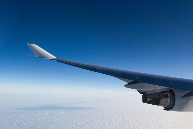 Beautiful shot from an airplane window of the wings over the clouds Free Photo