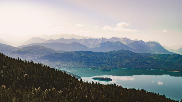 Beautiful shot of a high altitude lake surrounded by green mountains with sky Free Photo
